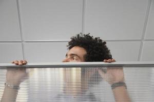 Büroangestellter späht über Kabinenwand
