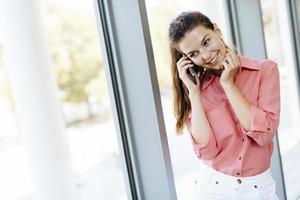 schöne Frauen, die aus dem Büro anrufen und lächeln foto
