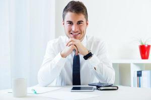 junger hübscher Mann, der in seinem Büro arbeitet. foto