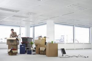 Geschäftsfrau, die Kartons im Büro auspackt foto