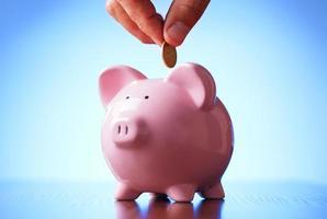 Mann, der eine Münze in ein Sparschwein legt