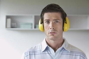Mann, der Gehörschutz im Büro trägt foto
