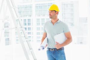 Handwerker mit Blaupausen und Zwischenablage im Büro foto