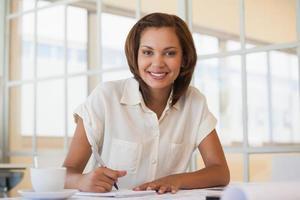 lächelnde Geschäftsfrau, die an Blaupause im Büro arbeitet foto