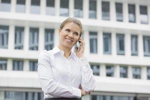 lächelnde Geschäftsfrau, die Handy außerhalb des Büros benutzt foto
