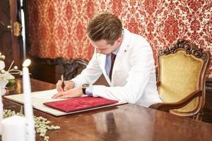 Bräutigam unterschreibt das Buch foto
