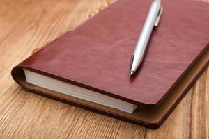 Notizblock mit Stift auf Holztisch foto