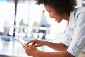 lächelnde junge Frau in einem Büro mit einer Tablette