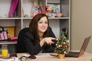 freudiges Mädchen im Büro mit einem Weihnachtsbaum foto