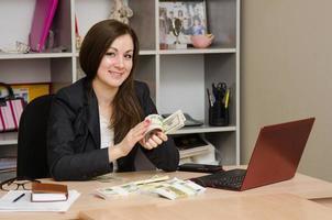 Mädchen im Büro dreht glücklich das Geld eine Packung foto