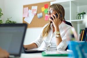Geschäftsfrau, die mit Handy in ihrem Büro arbeitet. foto