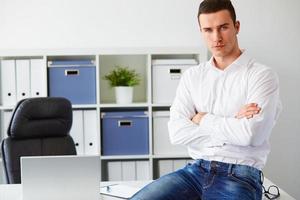 Geschäftsmann sitzt auf Schreibtisch mit verschränkten Armen im Büro foto