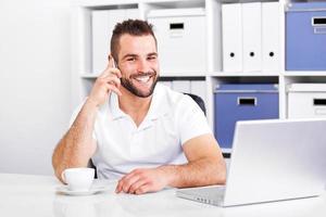 glücklicher Geschäftsmann, der am Telefon spricht foto