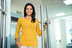 glückliche Geschäftsfrau, die im Amt steht foto