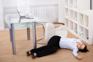 Geschäftsfrau fiel auf dem Boden in Ohnmacht foto