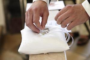 Bräutigam nehmen Ringe aus dem Kissen foto