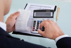 Geschäftsmann, der Quittung hält, während Kosten im Amt berechnet foto