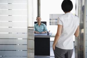 Mann spricht mit Frau, die in der Bürotür steht foto