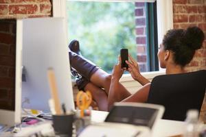 Geschäftsfrau auf Handy, die im modernen Büro entspannt foto