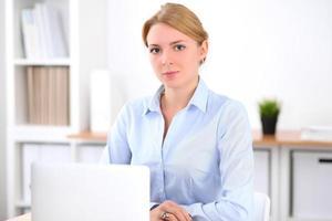 junge blonde Geschäftsfrau mit Laptop im Büro