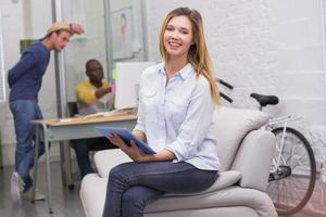 Gelegenheitsfrau, die digitales Tablett mit Kollegen hinter im Büro verwendet foto