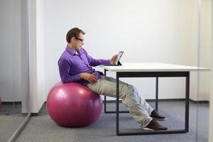 junger Mann auf Stabilitätsball, der mit Tablette im Büro arbeitet foto