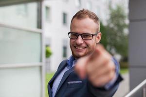 junger Geschäftsmann mit Bart, der vor Bürogebäude steht. foto