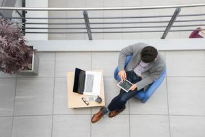 junger asiatischer Geschäftsmann mit Tablette, Handy im Büro foto