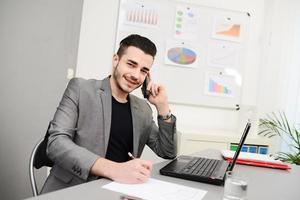junger Mann im Büro, der an Laptop und Telefon arbeitet foto