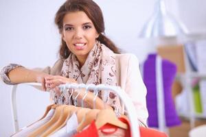 schöne junge Stylistin in der Nähe von Rack mit Kleiderbügeln foto