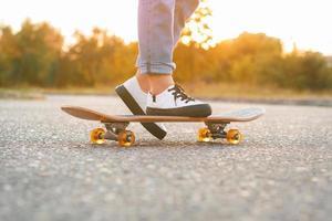 Mädchen, das auf einem Skateboard steht. Füße und Skateboard.