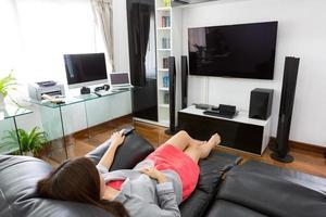 junge Geschäftsfrau, die Fernsehen im modernen Hauptbüro sieht foto