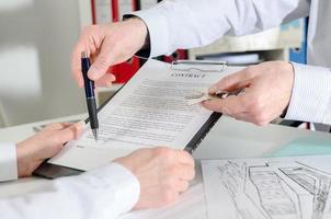 Makler zeigt, wo der Immobilienvertrag zu unterzeichnen ist foto