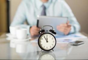 Nahaufnahmewecker, der Zeit in der Geschäftsstelle anzeigt foto