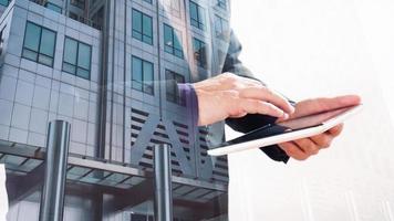 Doppelbelichtung des Bürogebäudes mit dem Geschäftsmann, der Tablettbildschirm berührt foto