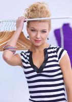 schöne junge Stylistin in der Nähe von Rack mit Kleiderbügeln im Büro foto