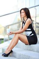 lächelnde junge kluge Geschäftsfrau, die Kaffeepause im Büro hat foto