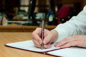 Mann schreibt etwas auf ein weißes Papier. Büroarbeit