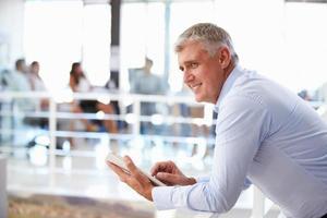 Porträt des Mannes mittleren Alters im Büro mit Tablette foto