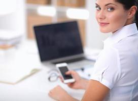Geschäftsfrau, die Nachricht mit Smartphone, das im Büro sitzt, sendet foto