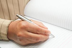macht eine Notiz im Notizbuch.