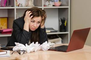 Mädchen am Computer mit einem Bündel zerknittertes Blatt Papier foto