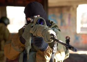 Armeemann mit Maske mit großem Gewehr foto