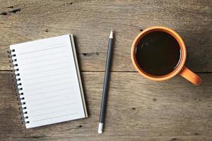 Kaffee und Notizbuch auf hölzernem Hintergrund foto