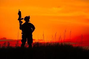 Silhouette des Militärsoldaten oder des Offiziers mit den Waffen bei Sonnenuntergang foto