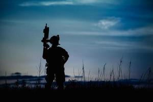 Silhouette eines Militärsoldaten oder Offiziers mit Waffen in der Nacht. foto