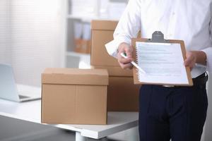 Zusteller mit Paket und einer Tablette, die im Büro stehen foto