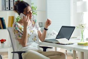 hübsche junge Frau mit ihrem Handy im Büro. foto