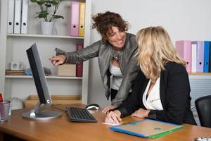 fröhliche Geschäftsfrauen, die im Büro an einem Computer arbeiten foto