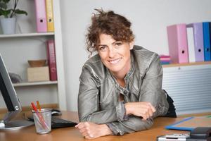 Frau im Büro auf ihrem Schreibtisch, der die Kamera betrachtet foto